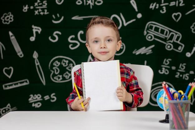 Garçon enfant mignon à faire leurs devoirs. enfant intelligent dessin au bureau. écolier. élève de l'école élémentaire dessin au lieu de travail. les enfants aiment apprendre. enseignement à domicile. retour à l'école. petit garçon à la leçon d'école
