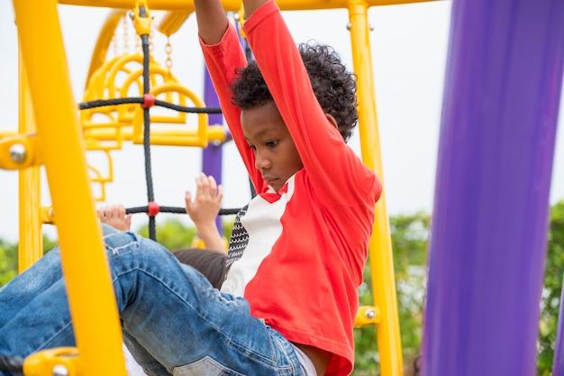 Garçon enfant s'amuser à jouer sur des jouets d'escalade pour enfants à l'école, retour à l'école