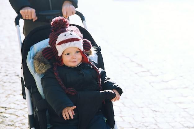 Garçon enfant souriant mignon dans un chapeau drôle en poussette passer des vacances d'hiver en famille au marché de noël à cesky krumlov, république tchèque, europe.