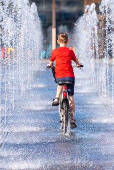 Garçon, enfant sur un vélo à cheval entre la fontaine au parc de la ville. garçon à vélo dans la rue au parc gorki à moscou, russie