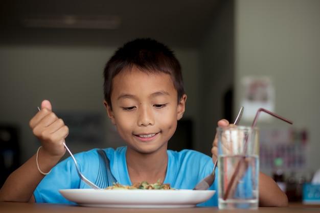 Garçon d'enfants asiatiques manger des aliments sains à la cantine ou à la cafétéria.