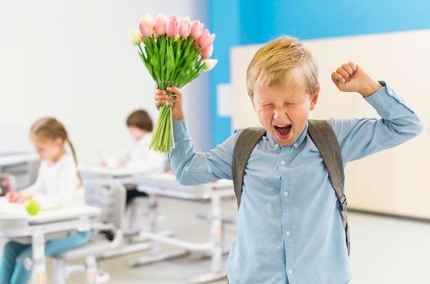 Garçon enthousiaste tenant un bouquet de fleurs