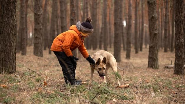 Le garçon entraîne son chien.