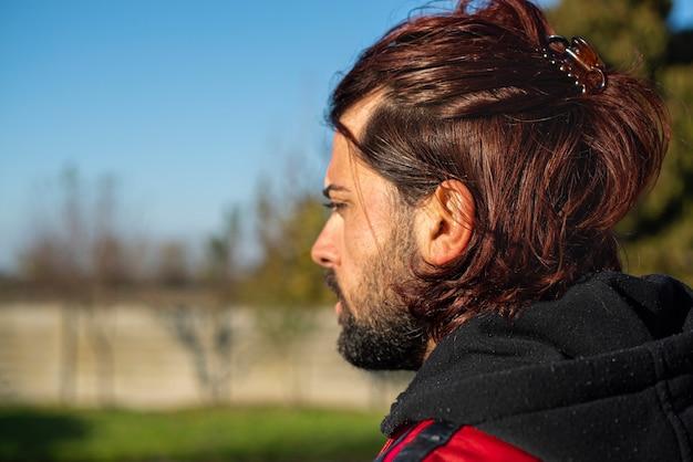 Garçon d'épaules aux cheveux longs en plein air par une journée ensoleillée