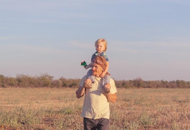 Garçon sur les épaules du père avec un avion jouet. papa et fils passent du temps dehors