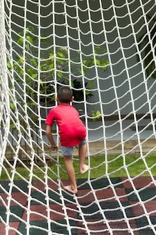 Garçon escaladant un filet de corde sur la cour de récréation.