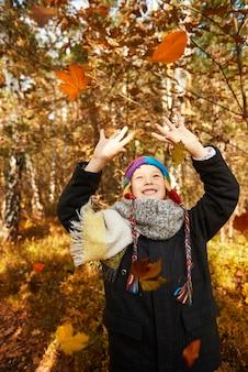Garçon essayant d'attraper autant de feuilles qu'il peut