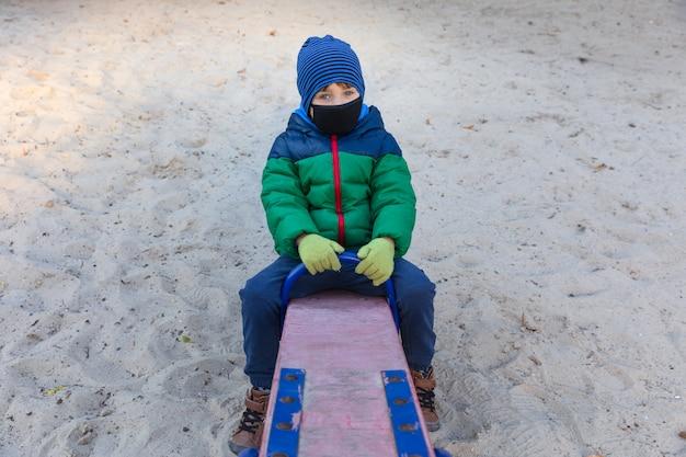 Garçon est assis sur une balançoire dans un masque médical