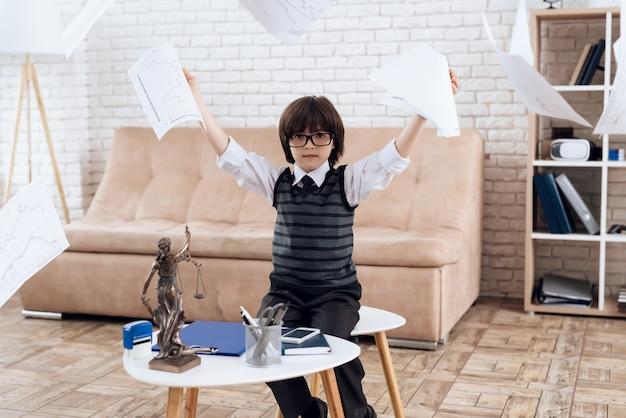 Un garçon est assis sur une chaise, des documents volent autour de lui