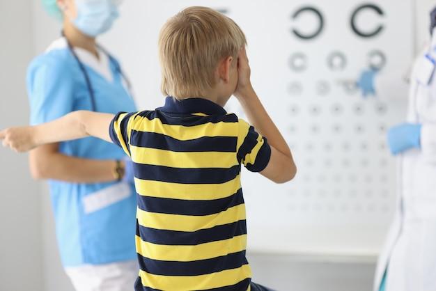 Le garçon est assis dos au rendez-vous de l'ophtalmologiste, regarde la table et répond aux questions.