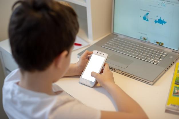 Le garçon est assis le dos derrière un ordinateur portable, tient un téléphone intelligent blanc dans ses mains, regarde dedans.