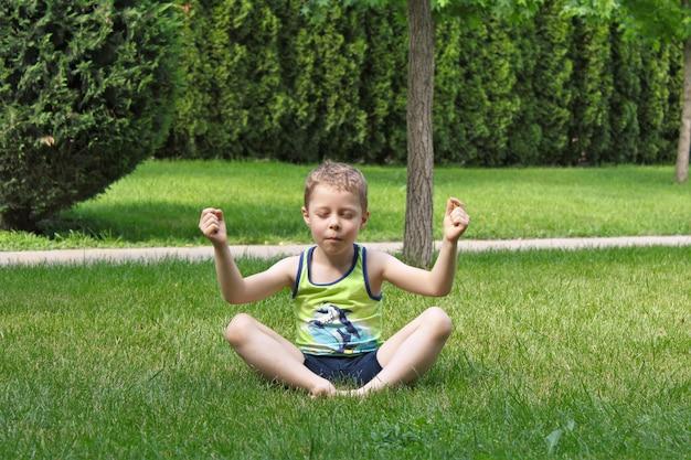Le garçon est assis sur l'herbe dans la position du lotus