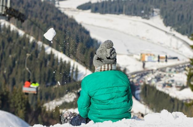 Le garçon est assis sur la pente enneigée d'une colline et lance une boule de neige sur fond de téléphérique, de forêt de conifères et de montagnes. station de ski. jour d'hiver.
