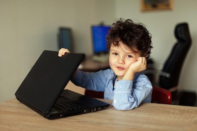 Le garçon est assis à la table avec l'ordinateur sourit et regarde l'ordinateur portable