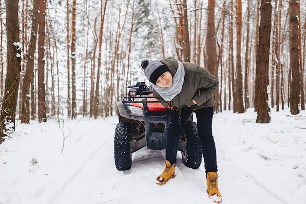 Un garçon est debout près d'un quad au milieu de la forêt