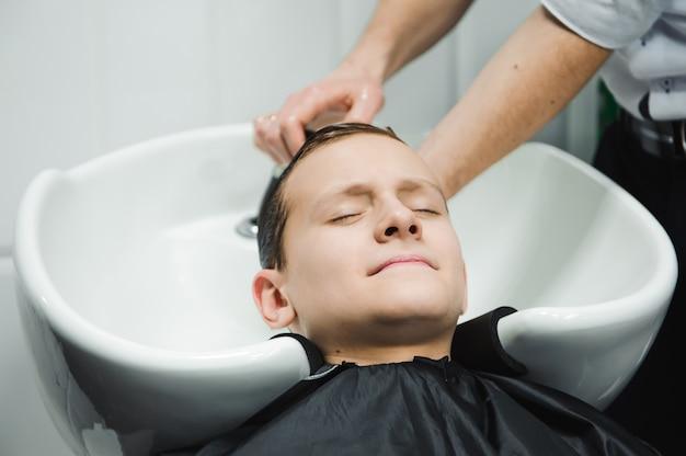 Un garçon est lavé par le coiffeur dans le salon de coiffure