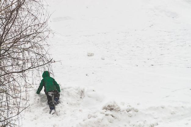 Garçon est monté dans la neige pendant la marche