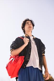 Garçon ethnique avec sac à dos rêveur à la recherche de suite