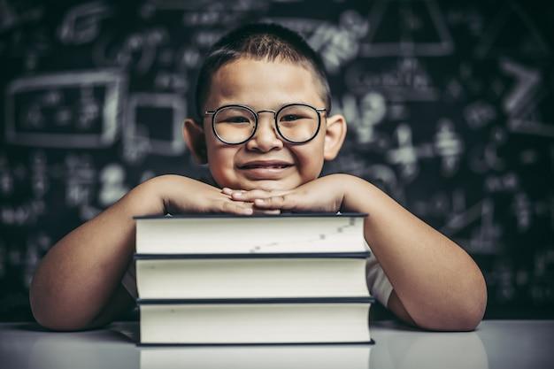 Un garçon étreignant une pile de livres.