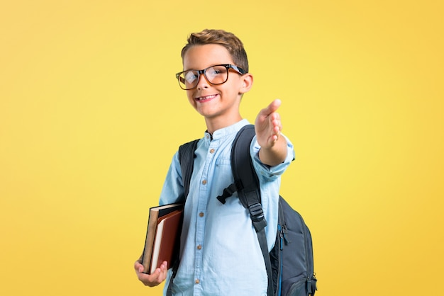 Garçon étudiant avec sac à dos et lunettes handshaking après une bonne affaire. retour à l'école