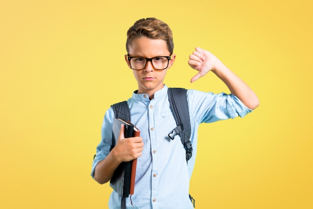 Garçon étudiant avec sac à dos et lunettes montrant le pouce en bas. retour à l'école
