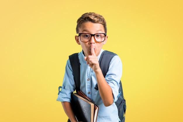 Garçon étudiant avec sac à dos et lunettes montrant un signe de fermeture de la bouche