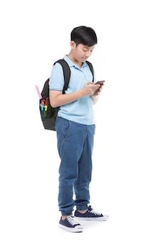 Garçon étudiant avec sac à dos et papeterie tenant le téléphone portable.