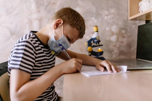 Garçon étudie à la maison tout en portant un masque de protection