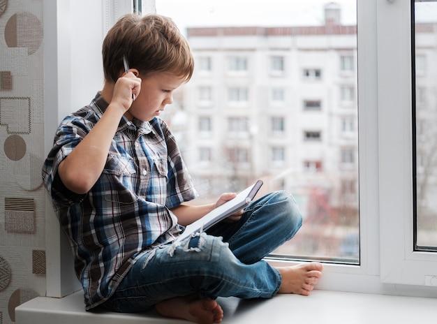 Garçon européen assis sur le rebord de la fenêtre contre la fenêtre et écrit de la poésie dans un cahier