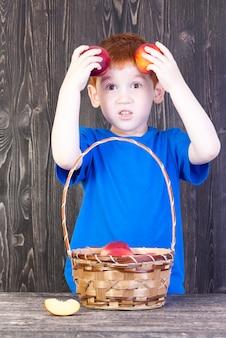 Un garçon européen aux cheveux rouges joue dans les pêches mûres qu'il garde près de la tête, gros plan