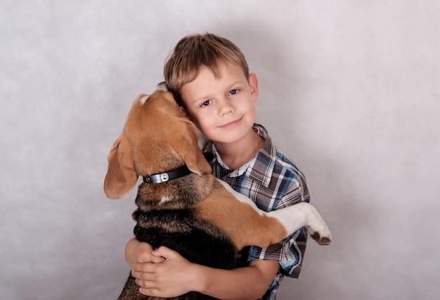 Un garçon européen et le chien élèvent beagle dans une étreinte joyeuse