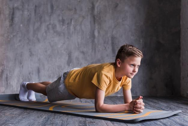 Garçon, exercice sur un tapis d'exercice devant le mur de béton