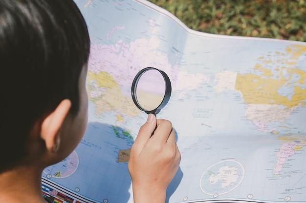 Garçon explorant la carte du monde à l'aide de la loupe