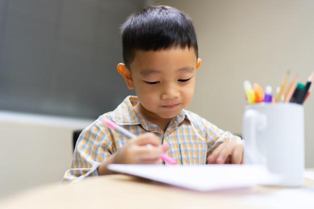 Garçon faire et sourire sur ses devoirs est facile