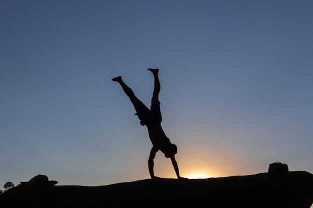 Garçon faisant des acrobaties sur un rocher au coucher du soleil en automne. espace de copie. rétro-éclairage.