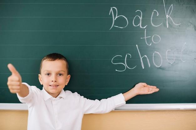 Garçon faisant un geste au tableau en classe