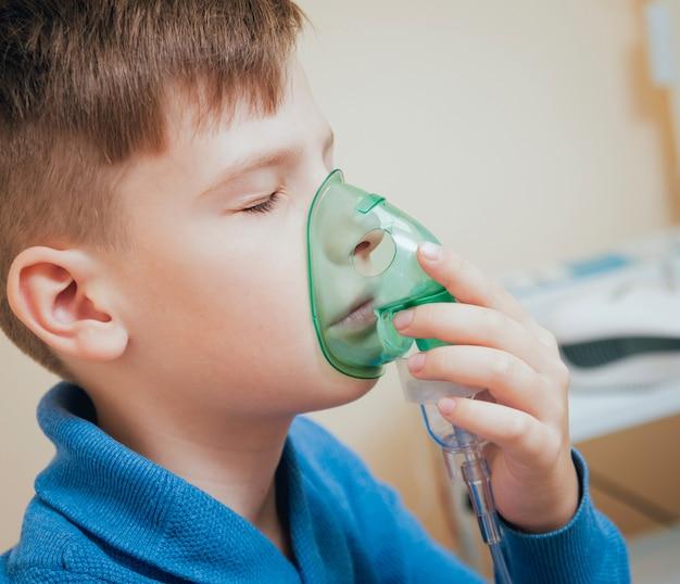 Garçon faisant l'inhalation avec un nébuliseur à la clinique.