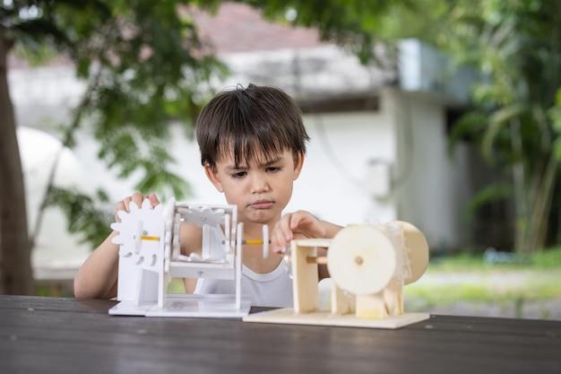 Un garçon et faites attention à apprendre le modèle de robot de mécanisme de simulation en bois sur table à la maison