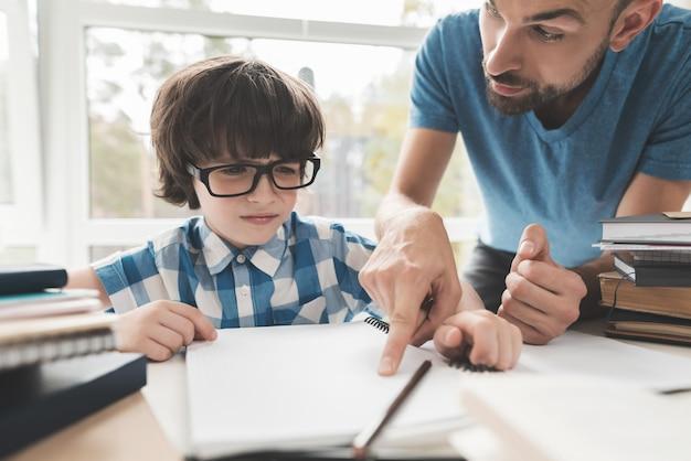 Un garçon fatigué des devoirs de papa l'aide.