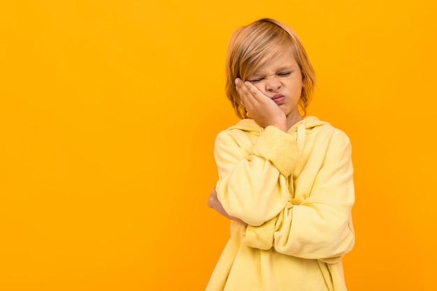 Garçon Fatigué Avec Un Panama Dans Un Sweat à Capuche Léger Sur Un Jaune Photo Premium