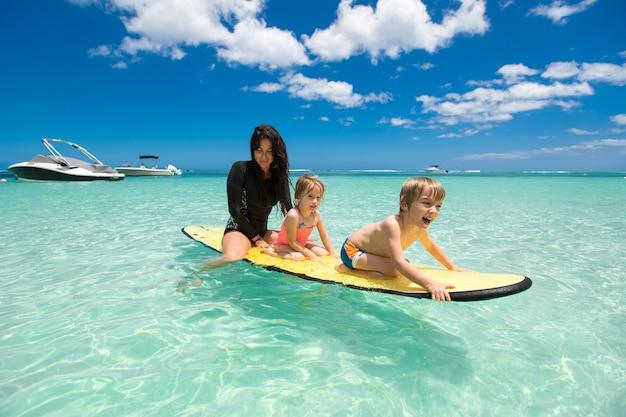 Garçon et femme jumeaux avec maman surfant dans l'océan sur un tableau noir