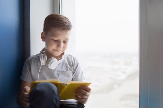 Garçon, fenêtre, lecture