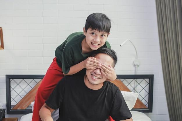 Garçon fermant les yeux de son père pour faire la surprise à la maison pendant la fête des pères