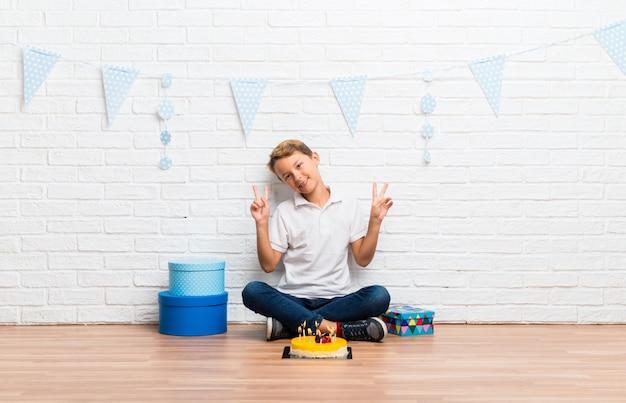 Garçon fête son anniversaire avec un gâteau souriant et montrant le signe de la victoire