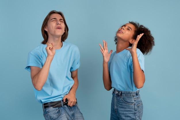 Garçon et fille de l'adolescence posant ensemble