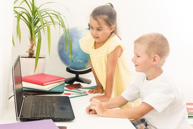 Garçon et fille à l'aide d'un ordinateur portable à l'école