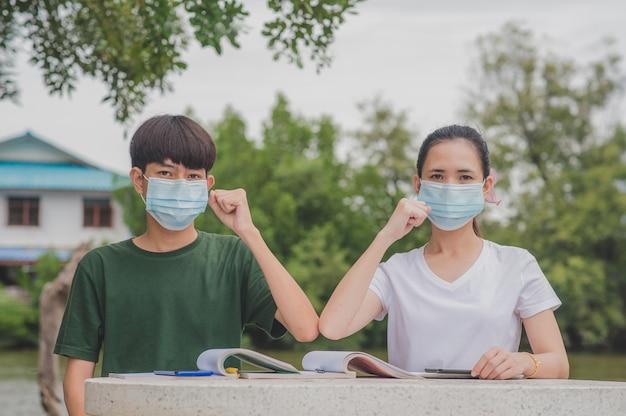 Un garçon et une fille asiatique retournent à l'école un masque facial et se serrent la main pour garder la nouvelle normale sans distanciation sociale touchante