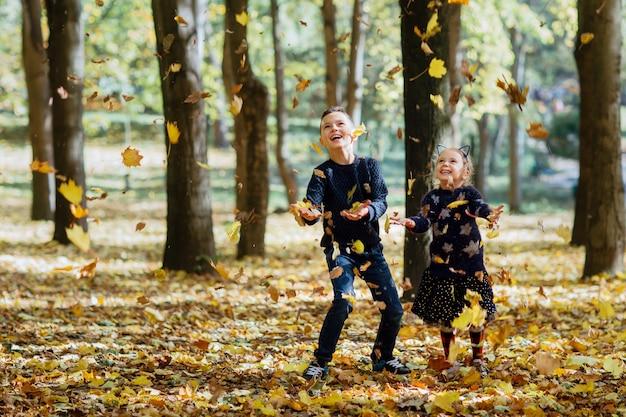 Garçon et fille attraper les feuilles qui tombent dans le parc automne