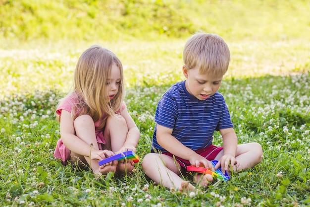 Garçon et fille blondes assises sur une pelouse d'herbe verte et jouent à un jouet en silicone anti-stress. pop it jouet sensoriel. soulagement du stress. jouet coloré de capteurs de silicone anti-stress