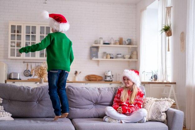 Garçon et fille en bonnet de noel et costume de noël jouant à la maison.